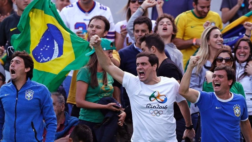 Fans cheer for Thomaz Bellucci, of Brazil, after he won a point against Rafael Nadal, of Spain, during their quarter final round match at the 2016 Summer Olympics in Rio de Janeiro, Brazil, Friday, Aug. 12, 2016. (AP Photo/Charles Krupa)
