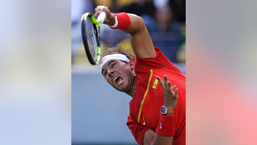 Rafael Nadal, of Spain, serves to Thomaz Bellucci, of Brazil, during their quarter final round match at the 2016 Summer Olympics in Rio de Janeiro, Brazil, Friday, Aug. 12, 2016. (AP Photo/Charles Krupa)
