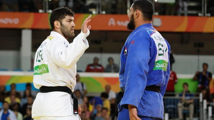 Egypt's Islam El Shehaby, blue, declines to shake hands with Israel's Or Sasson, white, after losing during the men's over 100-kg judo competition at the 2016 Summer Olympics in Rio Friday.