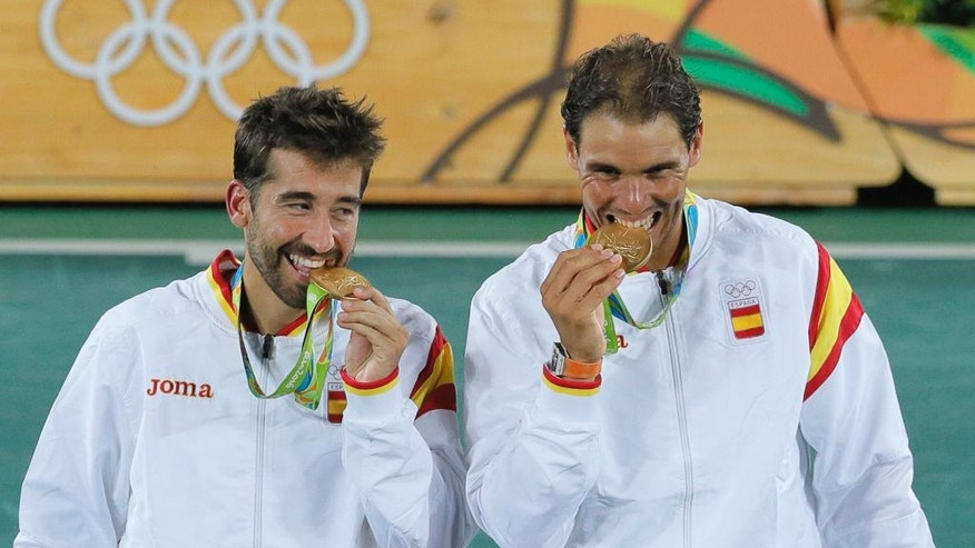 Spain Rafael Nadal, right, and Marc Lopez pose with the gold medals after defeating Romania's Horia Tecau and Florin Mergea in the men's doubles tennis competition at the 2016 Summer Olympics in Rio de Janeiro, Brazil, Friday, Aug. 12, 2016. (AP Photo/Vadim Ghirda)