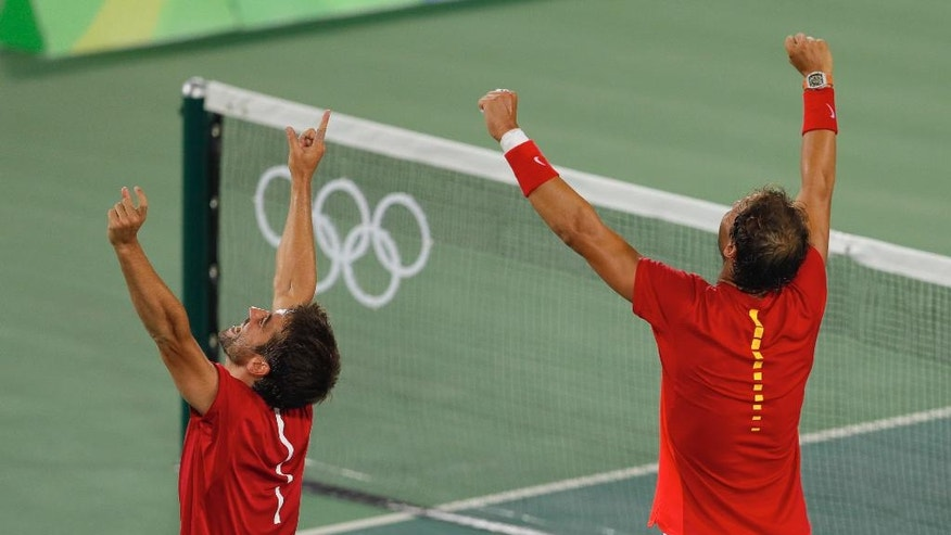 Spain Rafael Nadal, right, celebrates with doubles partner Marc Lopez after defeating Romania's Florin Mergea and Horia Tecau in the gold medal match of the men's doubles tennis competition at the 2016 Summer Olympics in Rio de Janeiro, Brazil, Friday, Aug. 12, 2016. (AP Photo/Vadim Ghirda)