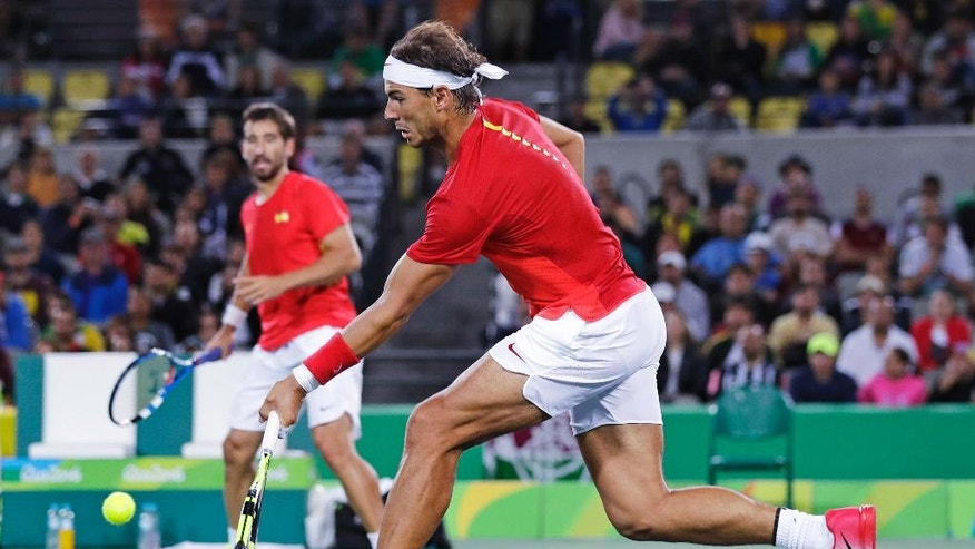 Rafael Nadal, of Spain, right, returns as his partner Marc Lopez watches in their match against Romania during the men's doubles final round at the 2016 Summer Olympics in Rio de Janeiro, Brazil, Friday, Aug. 12, 2016. (AP Photo/Charles Krupa)