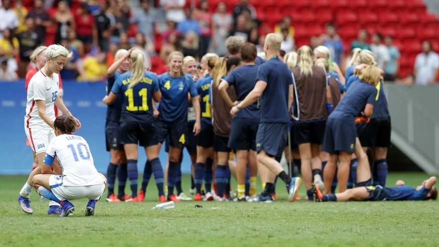 Aug. 12, 2016: United States' Megan Rapinoe and Carli Lloyd react as Sweden's players celebrate after a penalty shoot-out during a quarter-final match of the women's Olympic football tournament between the United States and Sweden in Brasilia