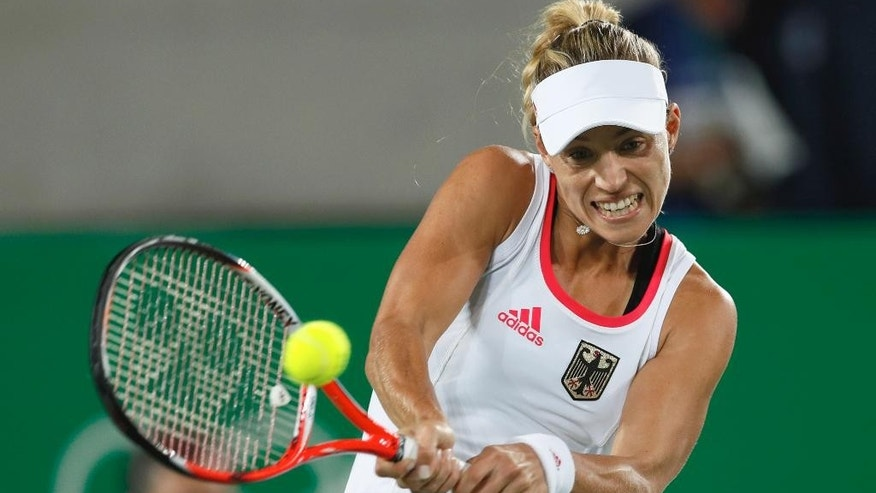 Germany's Angelique Kerber returns to Monica Puig of Puerto Rico in the gold medal match of the women's tennis competition at the 2016 Summer Olympics in Rio de Janeiro, Brazil, Saturday, Aug. 13, 2016. (AP Photo/Vadim Ghirda)