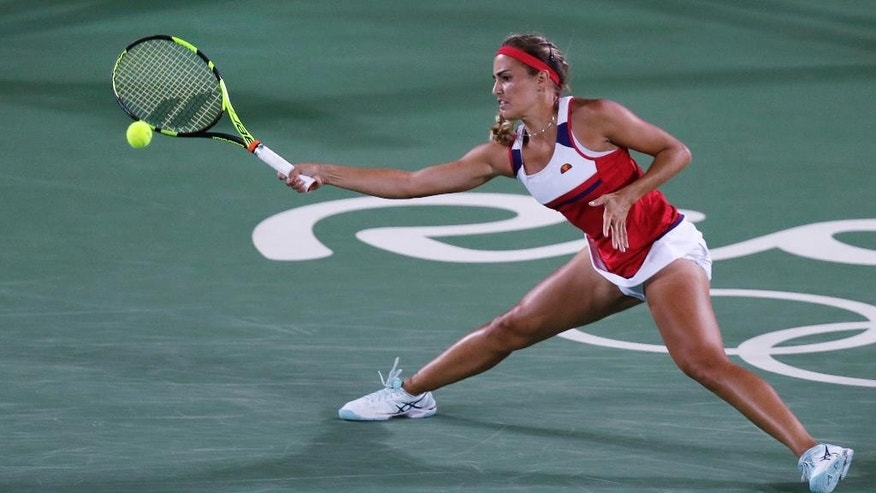 Monica Puig, of Puerto Rico, returns to Angelique Kerber, of Germany during their final round match at the 2016 Summer Olympics in Rio de Janeiro, Brazil, Saturday, Aug. 13, 2016. (AP Photo/Charles Krupa)