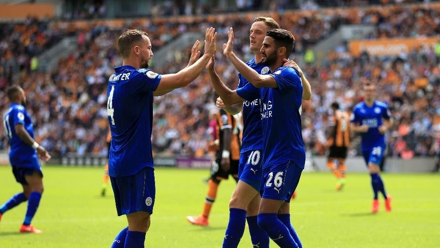 Leicester City's Riyad Mahrez, right, celebrates scoring his side's first goal of the game from the penalty spot during the Premier League soccer match at the KCOM Stadium, Hull, England, Saturday Aug. 13, 2016. (Nigel French / PA via AP)
