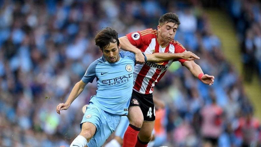 Manchester City's David Silva, left, and Sunderland's Lynden Gooch in action during their English Premier League soccer match at the Etihad Stadiium, Manchester, England, Saturday Aug. 13, 2016. (Anthony Devlin / PA via AP)