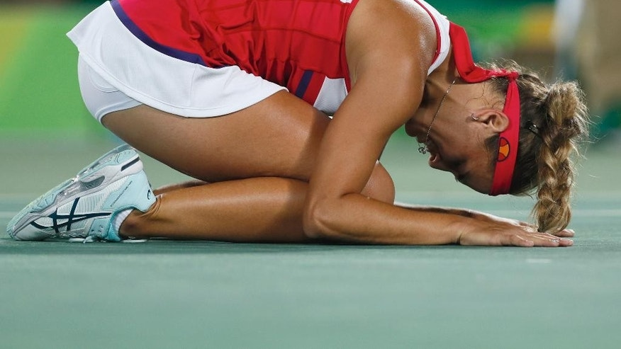 Monica Puig of Puerto Rico kneels on the court after winning the gold medal match in the women's tennis competition at the 2016 Summer Olympics in Rio de Janeiro, Brazil, Saturday, Aug. 13, 2016. (AP Photo/Vadim Ghirda)
