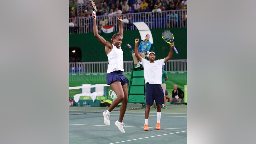 Venus Williams, left, and her partner Rajeev Ram, of the United States, celebrate after defeating India during their semi-final mixed doubles match at the 2016 Summer Olympics in Rio de Janeiro, Brazil, Saturday, Aug. 13, 2016. The United States advances to the gold medal game. (AP Photo/Charles Krupa)