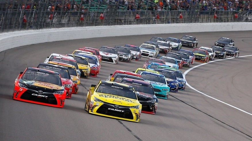 KANSAS CITY, KS - MAY 07: Martin Truex Jr., driver of the #78 Bass Pro Shops/TRACKER Boats Toyota Toyota, and Matt Kenseth, driver of the #20 Dollar General Toyota, lead the field at the start of the NASCAR Sprint Cup Series Go Bowling 400 at Kansas Speedway on May 7, 2016 in Kansas City, Kansas. (Photo by Jamie Squire/Getty Images)