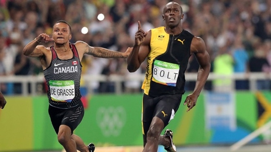 Jamaica's Usain Bolt celebrates as he crosses the line to win gold in the men's 100-meter final with Canada's Andre de Grasse during the athletics competitions of the 2016 Summer Olympics at the Olympic stadium in Rio de Janeiro, Brazil, Sunday, Aug. 14, 2016.
