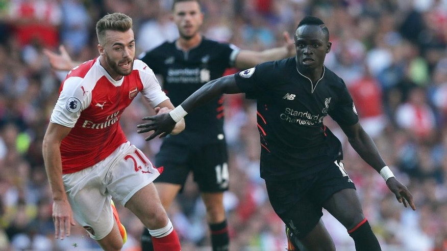 Liverpool's Sadio Mane, right, breaks away from Arsenal's Calum Chambers during the English Premier League soccer match between Arsenal and Liverpool at the Emirates Stadium in London, Sunday Aug. 14, 2016. (AP Photo/Tim Ireland)