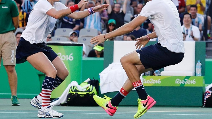 Bethanie Mattek-Sands, of the United States, left, runs into the arms of partner Jack Sock, after winning their mixed doubles gold medal match against Venus Williams and Rajeev Ram, of the United States, at the 2016 Summer Olympics in Rio de Janeiro, Brazil, Sunday, Aug. 14, 2016. (AP Photo/Charles Krupa)