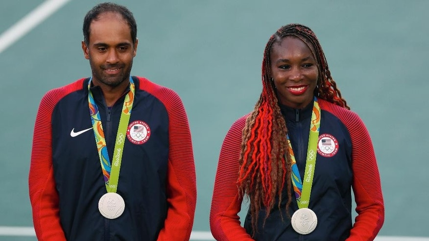 Silver medalists Venus Williams and Rajeev Ram, of the United States pose with their medals during the medals ceremony of the mixed doubles tennis competition at the 2016 Summer Olympics in Rio de Janeiro, Brazil, Sunday, Aug. 14, 2016. Bethanie Mattek-Sands, of the United States, and Jack Sock, won gold and the Czech Republic's Lucie Hradecka and Radek Stepanek won bronze. (AP Photo/Vadim Ghirda)