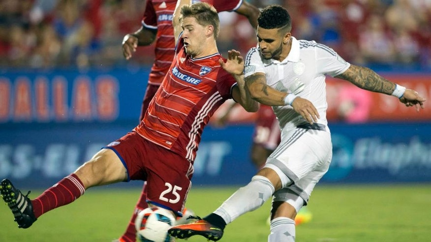 Aug 13, 2016; Dallas, TX, USA; Sporting Kansas City forward Dom Dwyer (14) scores his second goal while defended by FC Dallas defender Walker Zimmerman (25) in the second half at Toyota Stadium. FC Dallas and Sporting Kansas City tied 2-2. Mandatory Credit: Tim Heitman-USA TODAY Sports