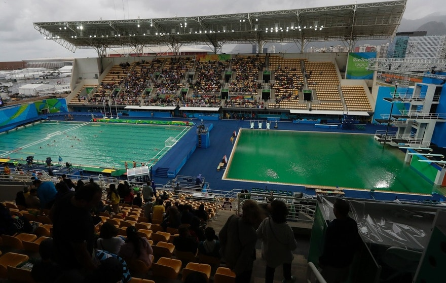 FILE - In this Aug. 10, 2016 file photo, the water of the diving pool at right appears a murky green as the water polo pool at left appears a greener color than the previous day during a preliminary round match between United States and France in the Maria Lenk Aquatic Center at the 2016 Summer Olympics in Rio de Janeiro, Brazil. Halfway through the Olympics, Rio de Janeiro is still struggling with a litany of problems that have underlined the challenges of taking the games away from their traditional territories, and made clear the games may not go to untested regions again in the near future.  (AP Photo/Matt Dunham, File)