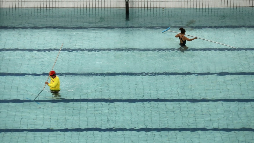 Technicians and lifeguards drain water from the synchronised swimming pool before it is replaced.