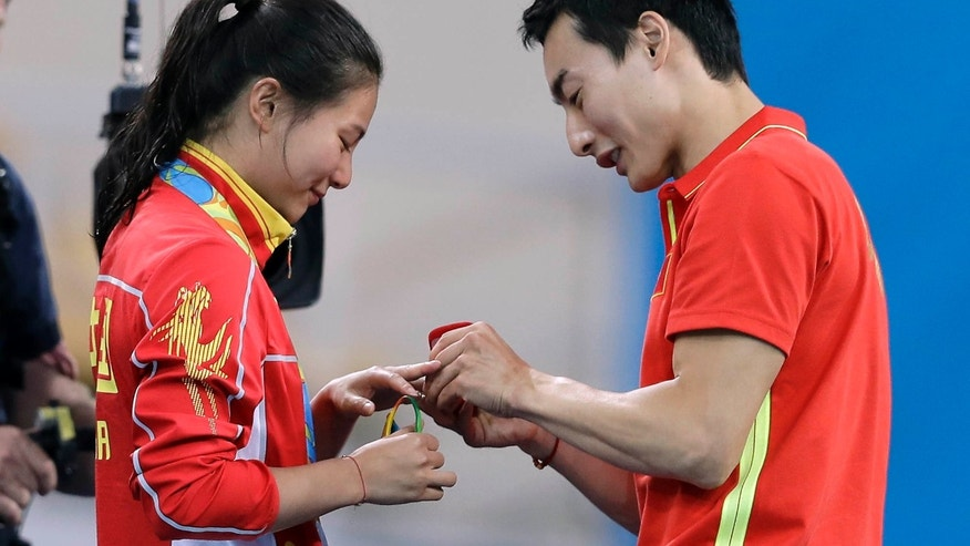 Aug. 14, 2016: China's silver medalist He Zi, left, receivers a marriage proposal by China's diver Qin Ki, right, during the medal ceremony for the the women's 3-meter springboard diving final in the Maria Lenk Aquatic Center at the 2016 Summer Olympics in Rio de Janeiro, Brazil
