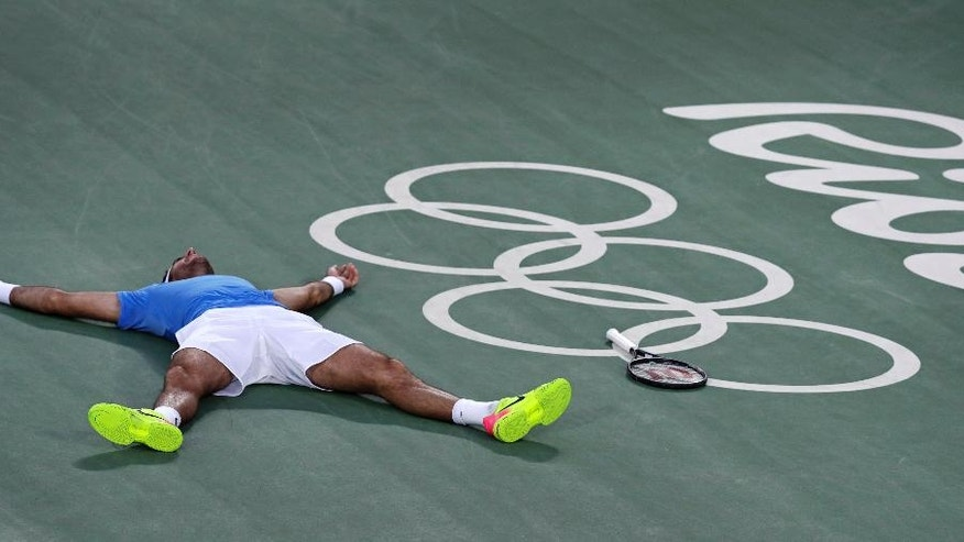 Juan Martin del Potro, of Argentina, drops to the court as he celebrates his victory over Rafael Nadal, of Spain, during their semi-final round match at the 2016 Summer Olympics in Rio de Janeiro, Brazil, Saturday, Aug. 13, 2016. (AP Photo/Charles Krupa)