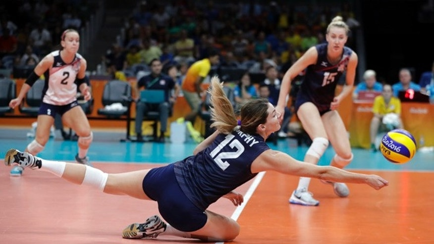 United States' Kelly Murphy (12) dives for the ball as teammates Kayla Banwarth (2) and Kim Hill watch during a women's quarterfinal volleyball match against Japan at the 2016 Summer Olympics in Rio de Janeiro, Brazil, Tuesday, Aug. 16, 2016.