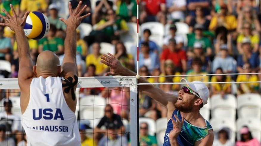 Brazil's Alison Cerutti, right, hits over United States' Phil Dalhausser during a men's beach volleyball quarterfinal match at the 2016 Summer Olympics in Rio de Janeiro, Brazil, Monday, Aug. 15, 2016. (AP Photo/Marcio Jose Sanchez)