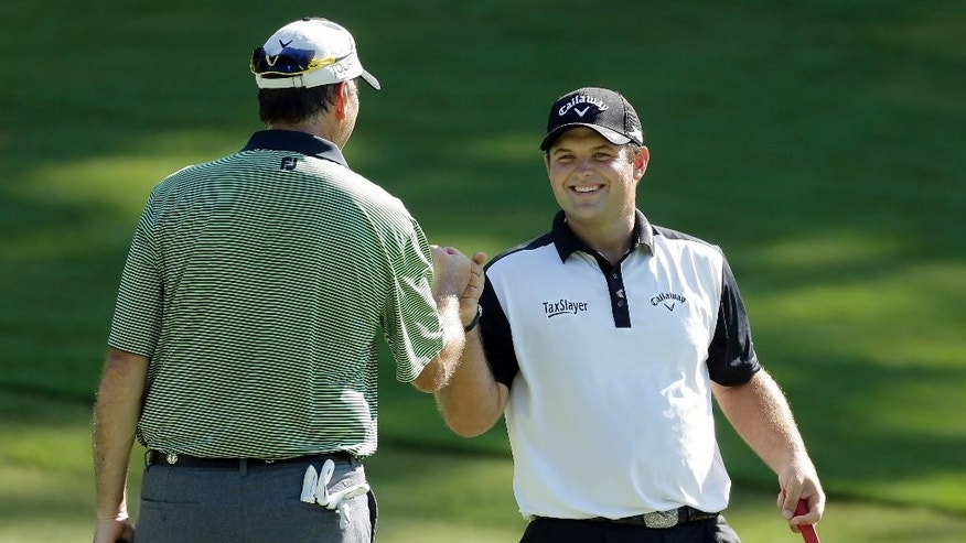 Patrick Reed, right, is congratulated by Tom Nelson, left, after making a putt on the eighth hole during the pro-am for the Wyndham Championship golf tournament in Greensboro, N.C., Wednesday, Aug. 17, 2016. (AP Photo/Chuck Burton)