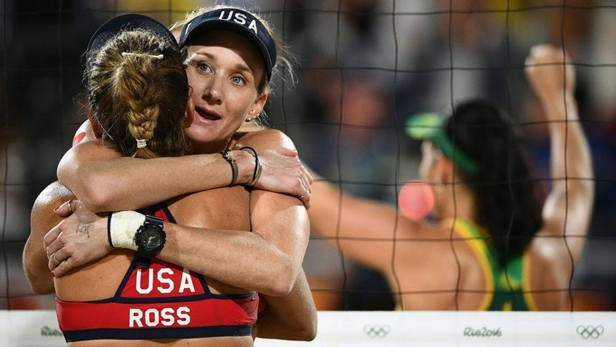 <p>USA's Kerri Walsh Jennings (2L) and USA's April Ross react after losing the women's beach volleyball semi-final match between USA and Brazil at the Beach Volley Arena in Rio de Janeiro on August 16, 2016, as part of the Rio 2016 Olympic Games. / AFP / Leon NEAL (Photo credit should read LEON NEAL/AFP/Getty Images)<br> </p>