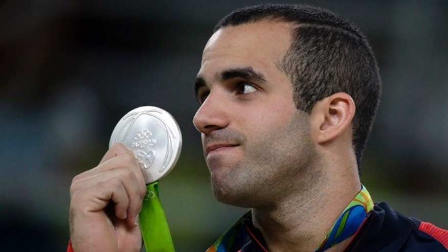 United States' Danell Leyva displays his silver medal for the parallel bars during the artistic gymnastics men's apparatus final at the 2016 Summer Olympics in Rio de Janeiro, Brazil, Tuesday, Aug. 16, 2016. (AP Photo/Rebecca Blackwell)