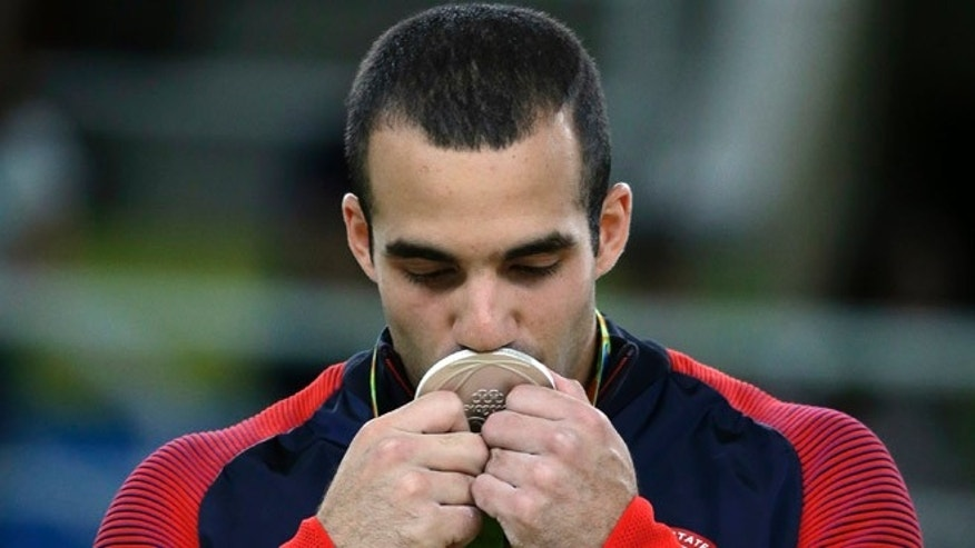 United States' Danell Leyva kisses his silver medal for the parallel bars during the artistic gymnastics men's apparatus final at the 2016 Summer Olympics in Rio de Janeiro, Brazil, Tuesday, Aug. 16, 2016. (AP Photo/Rebecca Blackwell)