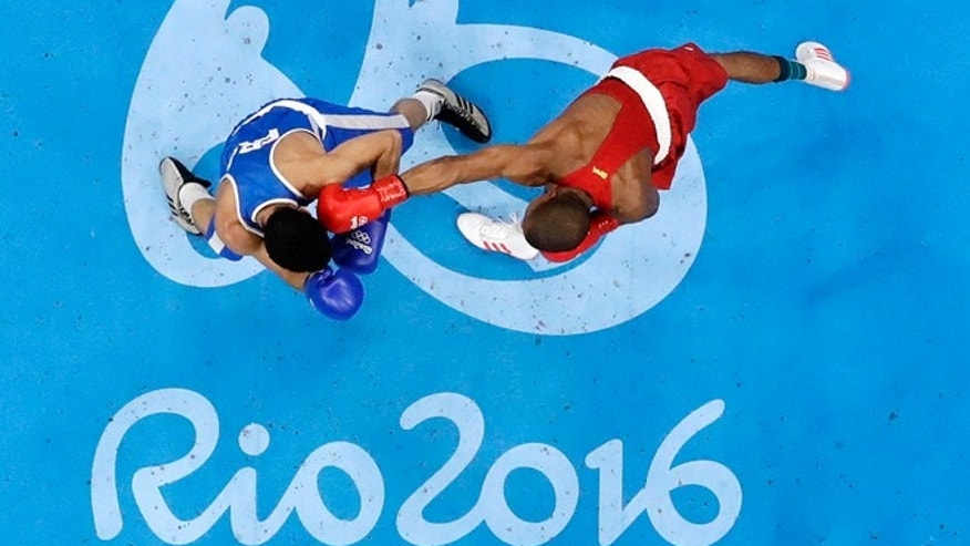 Brazil's Robson Conceicao, right, fights France's Sofiane Oumiha during a men's lightweight 60-kg final boxing match at the 2016 Summer Olympics in Rio de Janeiro, Brazil, Tuesday, Aug. 16, 2016.