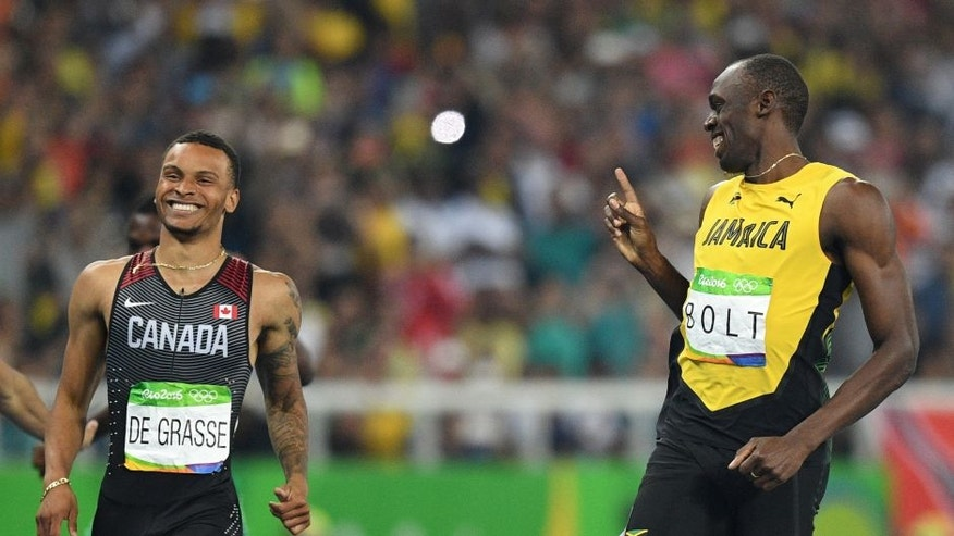 TOPSHOT - Jamaica's Usain Bolt (R) shares a laugh with de Canada's Andre De Grasse after their Men's 200m Semifinal during the athletics event at the Rio 2016 Olympic Games at the Olympic Stadium in Rio de Janeiro on August 17, 2016. / AFP / Johannes EISELE (Photo credit should read JOHANNES EISELE/AFP/Getty Images)