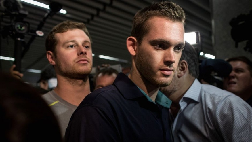 RIO DE JANEIRO, BRAZIL - AUGUST 18: U.S Olympic swimmers Gunnar Bentz and Jack Conger leave the police headquarters at International departures of Rio de Janiero's Galeo International airport on August 18, 2016 in Rio de Janiero, Brazil. The swimmers were removed from their flight departing for the United States by Brazilian authorities to give more information about a reported armed robbery earlier in the week which included fellow U.S swimmers Ryan Lochte and James Feign. (Photo by Chris McGrath/Getty Images)
