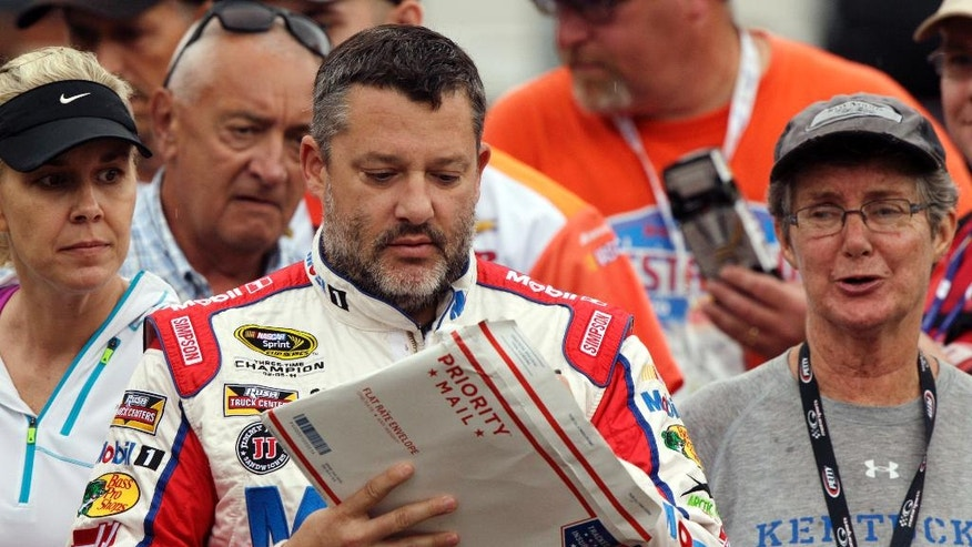 Tony Stewart signs an autograph as he walks through the pit area after practice for a NASCAR Sprint Series auto race on Friday, Aug. 19, 2016 in Bristol, Tenn. (AP Photo/Wade Payne)