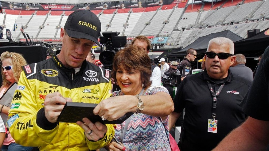 Carl Edwards signs an autograph as he walks through the pit area after practice for a NASCAR Sprint Series auto race on Friday, Aug. 19, 2016 in Bristol, Tenn. (AP Photo/Wade Payne)