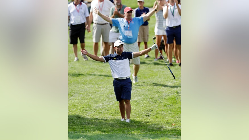 Nick Carlson acknowledges the crowd after his approach shot on the 10th green during a quarterfinal round of the U.S. Amateur golf tournament at Oakland Hills Country Club, Friday, Aug. 19, 2016, in Bloomfield Township, Mich. (AP Photo/Carlos Osorio)