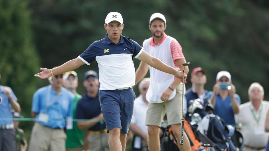 Nick Carlson tries body language to sway the ball closer to the hole on the 17th green during a quarterfinal round of the U.S. Amateur golf tournament at Oakland Hills Country Club, Friday, Aug. 19, 2016, in Bloomfield Township, Mich. (AP Photo/Carlos Osorio)