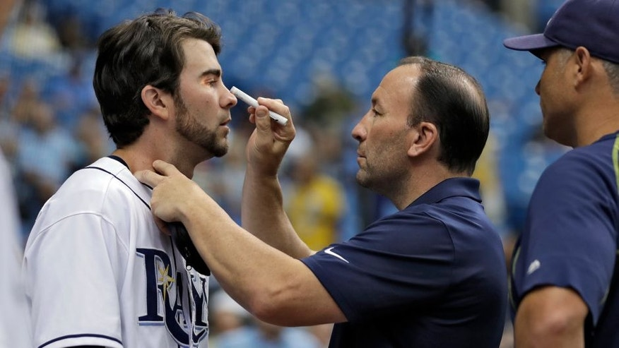Tampa Bay Rays trainer Ron Porterfield, center, checks on Nick Franklin, left, after Franklin was hit with a bat while in the on-deck circle during the first inning of an interleague baseball game Wednesday, Aug. 17, 2016, in St. Petersburg, Fla. Looking on is Rays manager Kevin Cash. Franklin left the game after the inning. (AP Photo/Chris O'Meara)