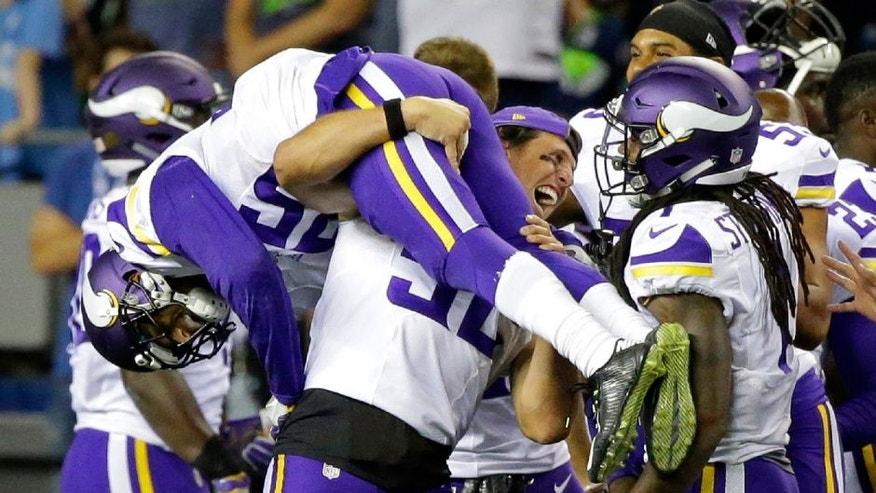 Minnesota Vikings cornerback Marcus Sherels is lifted by outside linebacker Chad Greenway, center, as they celebrate with wide receiver Troy Stoudermire, right, after Sherels intercepted a pass from Seattle Seahawks quarterback Trevone Boykin to score the go-ahead touchdown during the second half of a preseason NFL football game, Thursday, Aug. 18, 2016, in Seattle. The Vikings won 18-11.