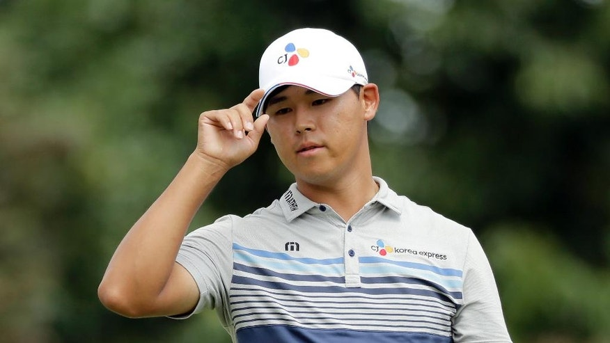 Si Woo Kim acknowledges the gallery on the ninth hole during the second round of the Wyndham Championship golf tournament in Greensboro, N.C., Friday, Aug. 19, 2016. (AP Photo/Chuck Burton)