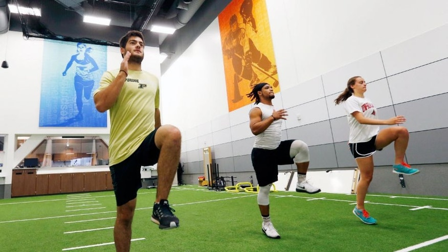 In this July 6, 2016 photo, from left, Stephen Kalina, Jaden Huff and Haley Nielsen go through workouts at the Mayo Clinic in Minneapolis. Mayo's new facility for high-level conditioning with noted performance trainer EXOS isn't just for elite athletes anymore. The general public can sign up for workouts similar to what NFL prospects take part in preparing for the combine, and weekend warriors are getting in more than just a good sweat before going to the office.