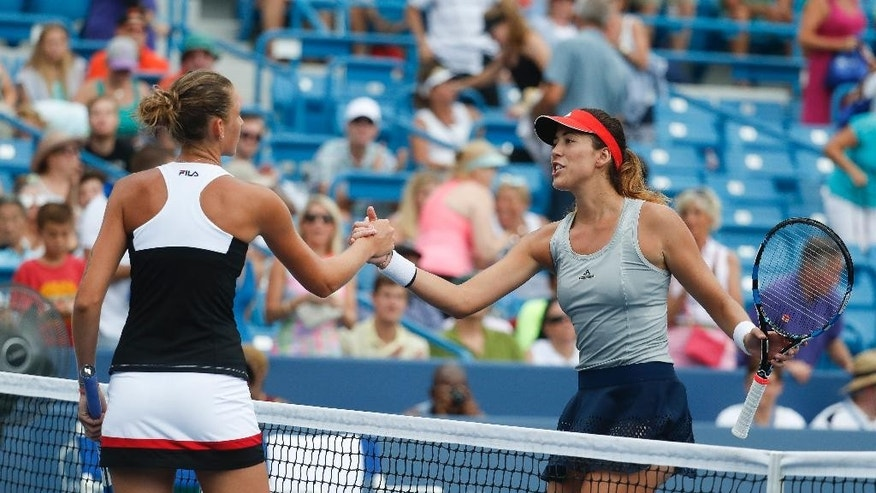 Karolina Pliskova, of the Czech Republic, left, shakes hands with Garbine Muguruza, of Spain, right after winning their match during the semifinals of the Western & Southern Open tennis tournament, Saturday, Aug. 20, 2016, in Mason, Ohio. Pliskova won 6-1, 6-3. (AP Photo/John Minchillo)