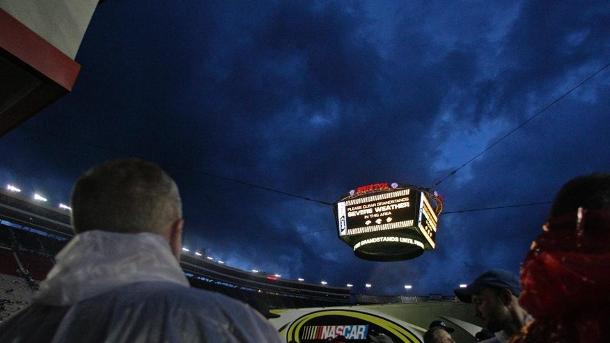 People look at the threatening sky as stormy weather delays the start of the NASCAR Sprint Cup Series auto race, Saturday, Aug. 20, 2016 ,in Bristol, Tenn. (AP Photo/Wade Payne)