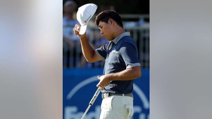 Si Woo Kim tips his hat to the crowd after finishing the 18th hole during the third round of the Wyndham Championship golf tournament in Greensboro, N.C., Saturday, Aug. 20, 2016. (AP Photo/Chuck Burton)