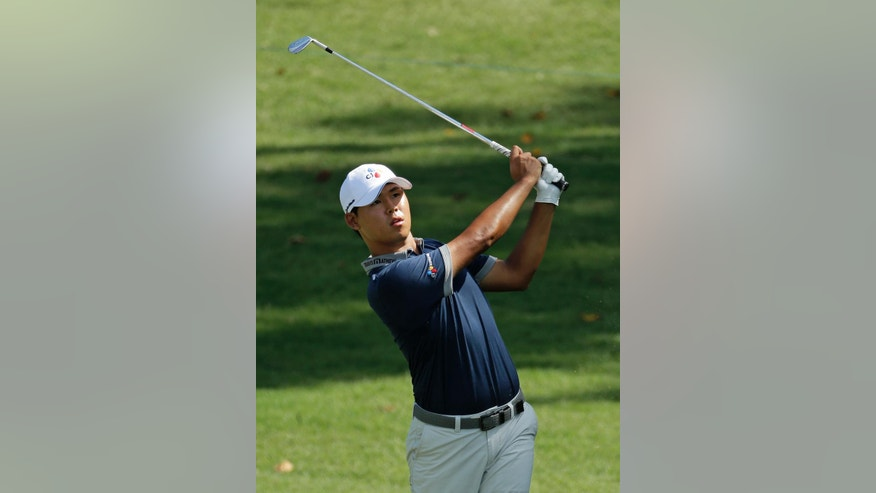 Si Woo Kim watches his approach shot on the ninth hole during the third round of the Wyndham Championship golf tournament in Greensboro, N.C., Saturday, Aug. 20, 2016. (AP Photo/Chuck Burton)