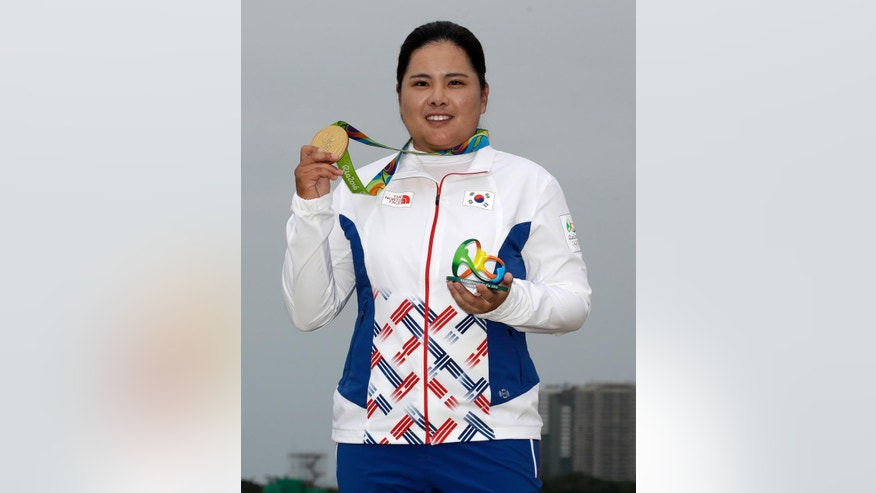 Inbee Park of South Korea, holds up her gold medal after the final round of the women's golf event at the 2016 Summer Olympics in Rio de Janeiro, Brazil, Saturday, Aug. 20, 2016. (AP Photo/Chris Carlson)