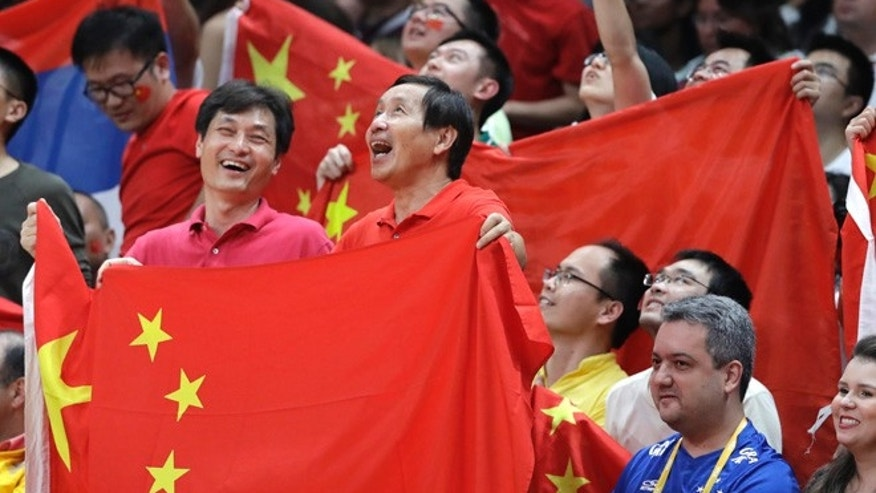 Fans hold the flag of China during a women's gold medal volleyball match between China and Serbia at the 2016 Summer Olympics in Rio de Janeiro, Brazil, Saturday, Aug. 20, 2016.