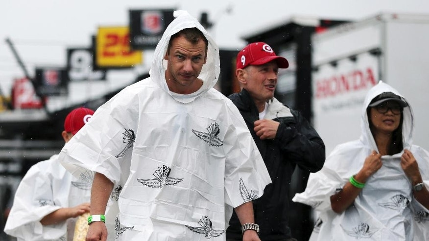 People walk in the rain in the garage area at Pocono Raceway before the Pocono IndyCar 500 auto race Sunday, Aug. 21, 2016, in Long Pond, Pa. The race was postponed due to the rain until Monday. (AP Photo/Mel Evans)