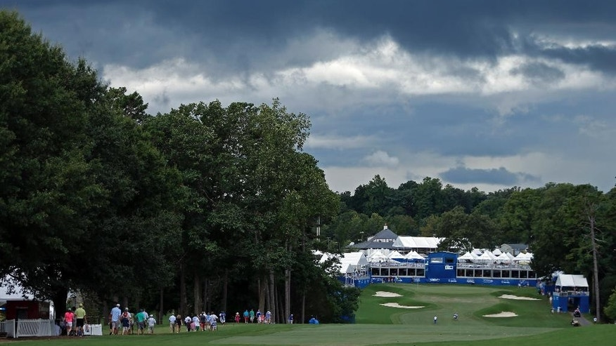 Fans walk down the 18th fairway under threatening clouds during a weather delay in the final round of the Wyndham Championship golf tournament in Greensboro, N.C., Sunday, Aug. 21, 2016. (AP Photo/Chuck Burton)