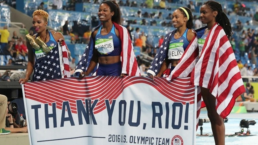 United States' Courtney Okolo, Natasha Hastings, Phyllis Francis and Allyson Felix hold a sign and wear their nation's flag after winning the gold in the women's 4x400 meter relay during athletics competitions at the Summer Olympics inside Olympic stadium in Rio de Janeiro, Brazil, Saturday, Aug. 20, 2016.