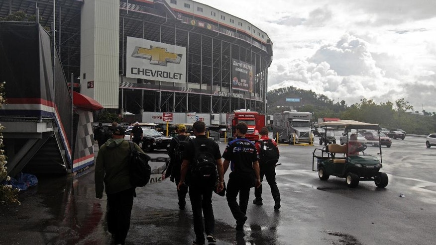 Crew members make their way into Bristol Motor Speedway under threatening skies for a NASCAR Sprint Cup Series auto race, Sunday, Aug. 21, 2016, in Bristol, Tenn. The race was delayed Saturday night due to severe weather. (AP Photo/Wade Payne)
